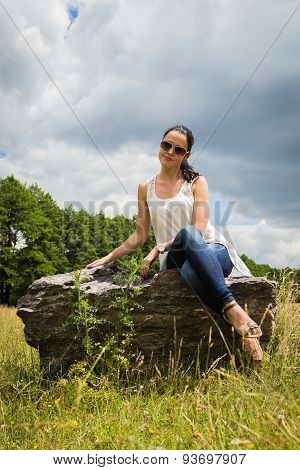 Beautiful girl in the field. Brunette sits on a rock, enjoying the outdoors and the sun.