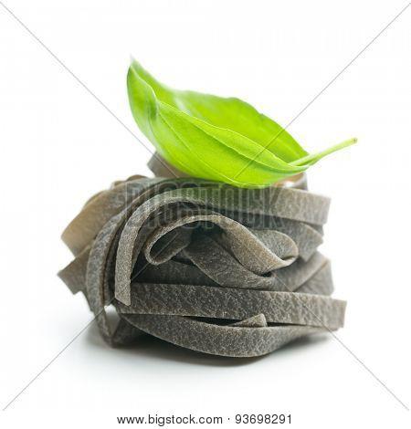 black tagliatelle pasta and basil leaf on white background