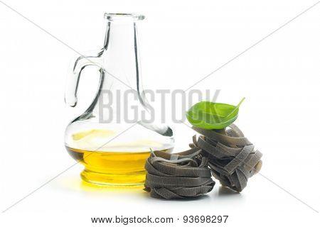 black tagliatelle pasta , oil and basil on white background