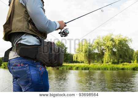 Fisherman on the river bank. Man fisherman catches a fish.