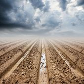 stock photo of rainy season  - Soil preparation on field and rainclouds in rainy season - JPG