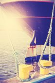 image of big-rig  - Vintage stylized big sailing ship moored to yellow bollard with ropes at sunset - JPG