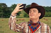 stock photo of cowboys  - Young farmer making selfie photo with smartphone - JPG