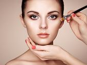 image of makeup artist  - Makeup artist applies skintone - JPG