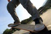 stock photo of skateboard  - closuep of skateboarder legs riding skateboard at skatepark - JPG