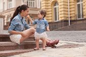 stock photo of eat me  - girl and mother have fun with ice cream on street - JPG