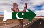 stock photo of pakistani flag  - Pakistan Flag wooden sign with desert road background - JPG