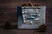 pic of pine cone  - Dry pine cones in denim box on brown wooden table - JPG