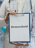 image of infirmary  - Doctor holds clipboard with hemorrhoid diagnosis written - JPG