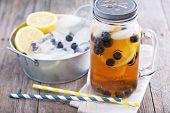 stock photo of mason  - Ice tea in mason jar mug with lemon and blueberries refreshing in hot summer day - JPG