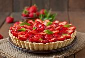 stock photo of tarts  - Tart with strawberries and whipped cream decorated with mint leaves - JPG