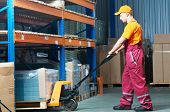 image of forklift  - male worker in warehouse working with hand forklift  - JPG