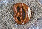 image of pretzels  - Fresh pretzels with sea salt on wooden table - JPG