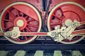 stock photo of locomotive  - big wheels a closeup of the vintage locomotive with the steam engine on railway tracks of red color - JPG