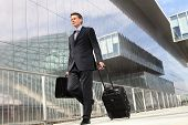 stock photo of trolley  - businessman walking with trolley and bag - JPG