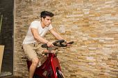stock photo of exercise bike  - Attractive young man exercising in gym - JPG