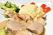foto of millet  - Dish consisting of baked pork loin millet gruel mushrooms tomatoes courgette and sauce on white plate