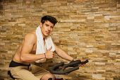 pic of exercise bike  - Attractive young man exercising in gym - JPG