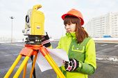 picture of theodolite  - female surveyor worker working with theodolite transit equipment at road construction site outdoors - JPG