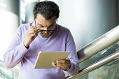 stock photo of squinting  - Closeup portrait dumbfounded flabbergasted man in black eyeglasses and purple sweater squinting eyes raising eyebrows looking closely at tablet isolated indoors office background - JPG