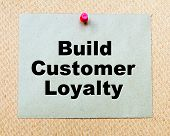 pic of loyalty  - Build Customer Loyalty written on paper note pinned with red thumbtack on wooden board - JPG