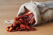 image of sleeping bag  - Dried tomatoes got enough sleep from canvas bag at wooden background - JPG