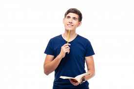 pic of thoughtfulness  - Thoughtful male student holding book and looking up isolated on a white background - JPG