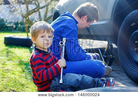 Little blond toddler boy and his father changing wheels on car with pneumatic wrench. Man in uniform teaching his son working with tools.
