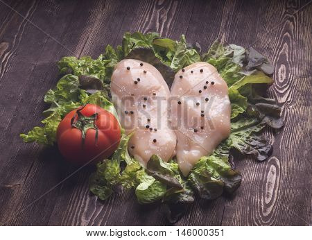 Raw chicken breast fillets. Raw chicken breasts and spices on wooden cutting board close up view.