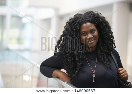 Smiling young black woman in the foyer of a modern building