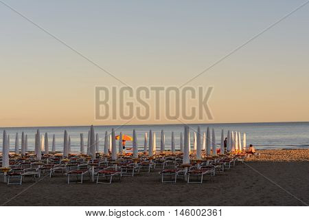 supplied folded sunshades and sunbeds on the sandy beach in Italy
