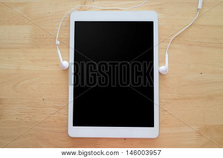 Office table with Blank tablet screen and earphone View from above tablet screen.