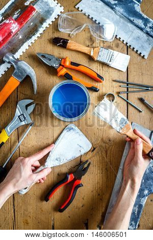 construction tools on a wooden table with blue paint with hands top view