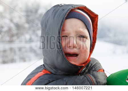 Little boy crying not wanting to walk outside in the winter landscape. Temper tantrum distress and emotional outburst concept.