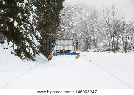 Snow plough making its way through the snowy country road clearing it of snow after blizzard. Professional winter services road conditions in winter concept.