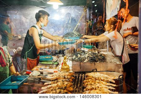 Young Woman Cooks And Sells Fish And Seafood