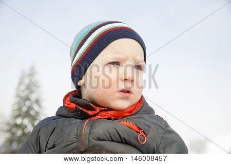 Blue eyed little boy in a winter landscape dressed in warm clothes enjoying the sun and observing nature. Active family lifestyle outdoor and natural childhood looking into the future concept.