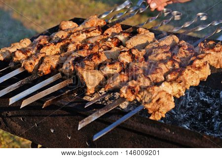 Male hand rotating meat pieces on skewer roasting in brazier