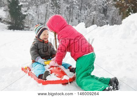 Brother and sister playing in snowy winter landscape enjoying the sledding bonding having winter fun. Active family lifestyle outdoor and natural childhood fun and carefree childhood concept.