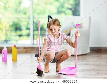 Little girl sweeping floor