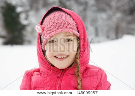 Beautiful girl with braids enjoying winter and snow dressed in warm clothes playing and catching some sun. Active family lifestyle outdoor and natural childhood carefree childhood concept.