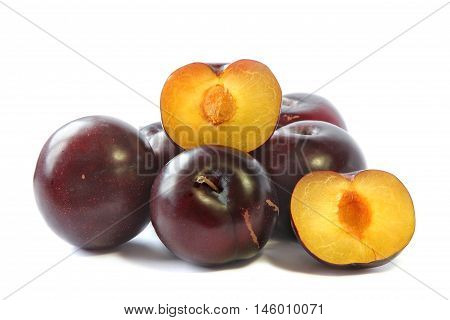 Plum and half of plum on a white background