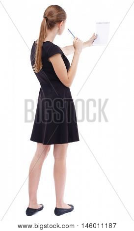 back view of stands woman takes notes in a notebook. girl watching. Isolated over white background. Blonde in a short black dress assures records in a notebook.
