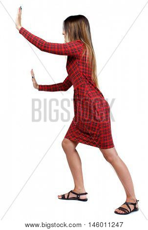 back view of woman pushes wall. backside view of person. The girl in red plaid dress that pushes it ahead.