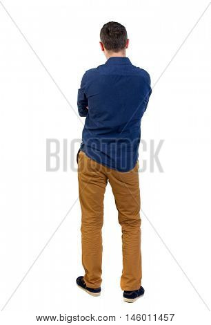 Back view of man . Standing young guy. man in a blue shirt with the sleeves rolled up, standing with her hands folded on his chest.