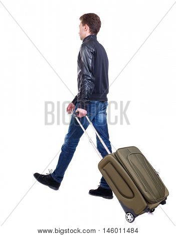 back view of walking man with suitcase. Curly guy in a black leather jacket goes by the handle suitcase.