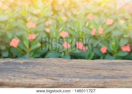 Empty table top with red small red flowers and green leaves for product display