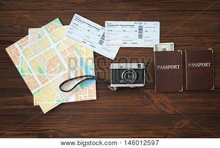 Vintage camera with map, passports and cash on wooden background