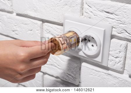 Woman hand putting euro banknotes into power socket on white wall