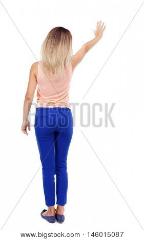 Back view of beautiful woman welcomes. Young teenager girl in jeans hand waving from. Blonde in blue pants waving to someone.